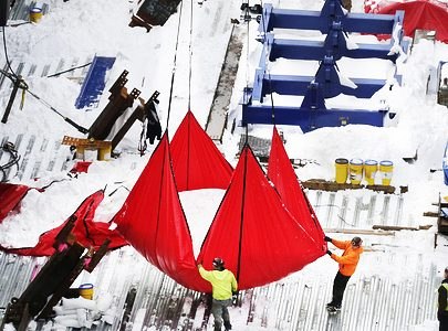 Workers guide a large, red tarp filled with snow as it is hoisted by a crane from the top deck of the Hudson Yards construction site, Monday, Jan. 25, 2016, in New York. Workers are clearing the construction site from the weekend snowstorm. (AP Photo/Mark Lennihan)